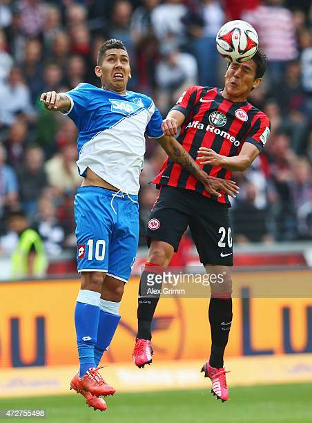 Roberto Firmino of Hoffenheim jumps for a header with Makoto Hasebe of Frankfurt during the Bundesliga match between Eintracht Frankfurt and 1899...