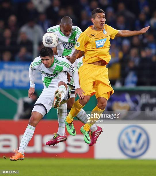 Roberto Firmino of Hoffenheim jumps for a header with Naldo nd Slobodan Medojevic of Wolfsburg the DFB Cup quarterfinal match between 1899 Hoffenheim...