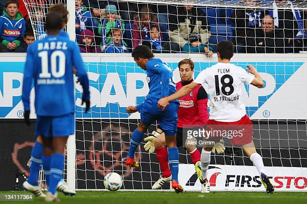 Roberto Firmino of Hoffenheim scores his team's first goal against goalkeeper Oliver Baumann of Freiburg during the Bundesliga match between 1899...
