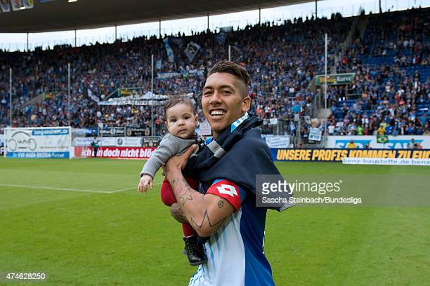 Roberto Firmino of Hoffenheim shows a child while he celebrates after winning the Bundesliga match against Hertha BSC Berlin at Wirsol...