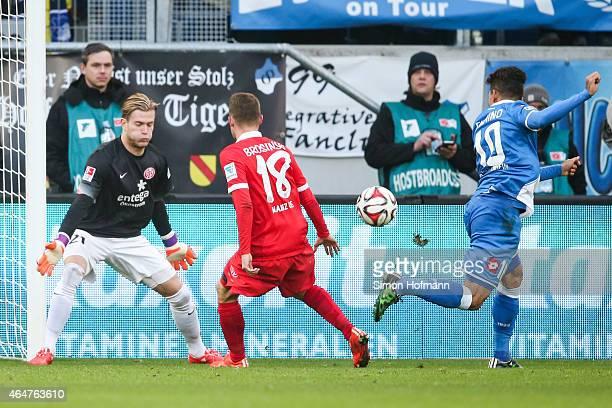 Roberto Firmino of Hoffenheim tries to score against goalkeeper Loris Karius and Daniel Brosinski of Mainz during the Bundesliga match between 1899...