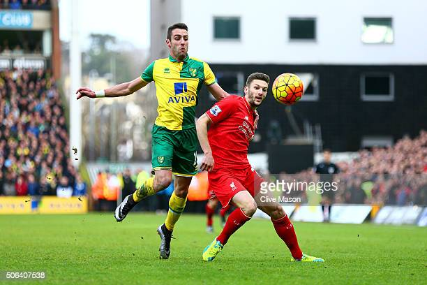 Roberto Firmino of Liverpool and Ivo Pinto of Norwich City compete for the ball during the Barclays Premier League match between Norwich City and...