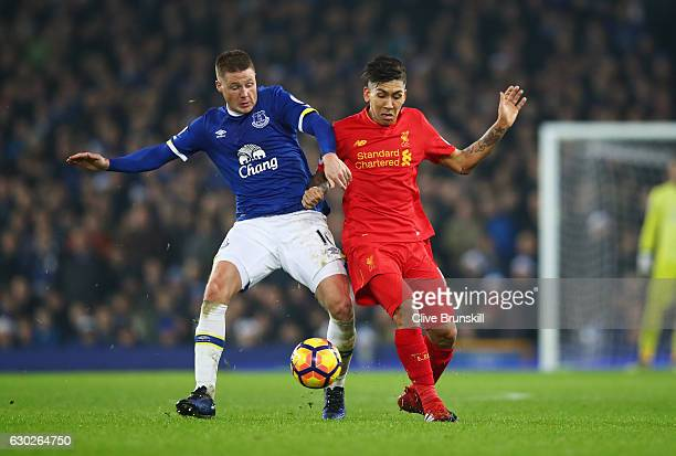 Roberto Firmino of Liverpool and James McCarthy of Everton battle for the ball during the Premier League match between Everton and Liverpool at...