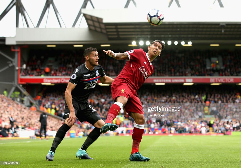 Roberto Firmino of Liverpool and Joel Ward of Crystal Palace battle for possession during the Premier League match between Liverpool and Crystal Palace at Anfield on August 19, 2017 in Liverpool, England.