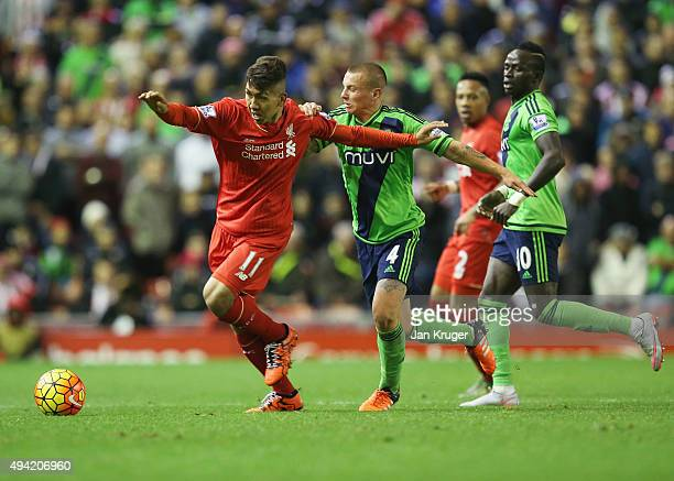 Roberto Firmino of Liverpool and Jordy Clasie of Southampton compete for the ball during the Barclays Premier League match between Liverpool and...