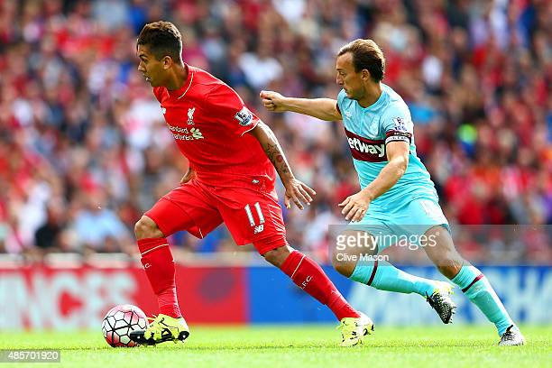 Roberto Firmino of Liverpool and Mark Noble of West Ham United compete for the ball during the Barclays Premier League match between Liverpool and...