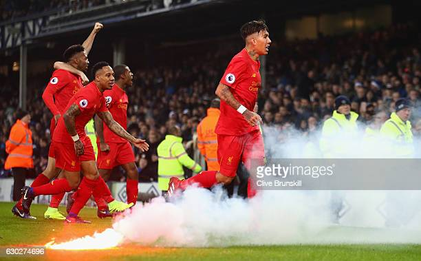 Roberto Firmino of Liverpool celebrates after team mate Sadio Mane has scored the winning goal during the Premier League match between Everton and...