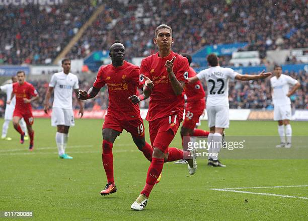 Roberto Firmino of Liverpool celebrates scoring his sides first goal during the Premier League match between Swansea City and Liverpool at Liberty...
