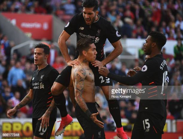 Roberto Firmino of Liverpool celebrates scoring his sides second goal with his Liverpool team mates during the Premier League match between Stoke...