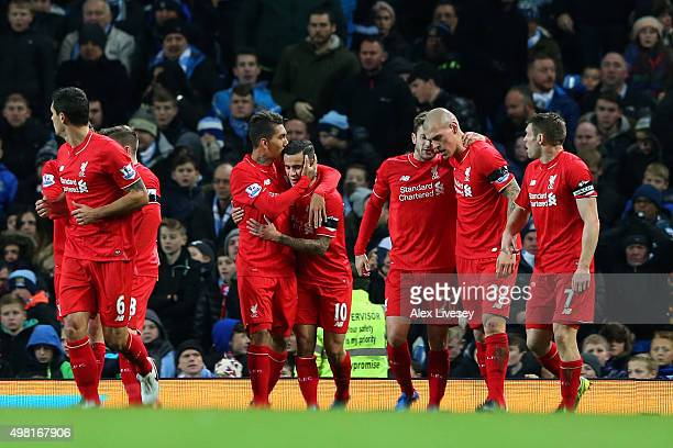 Roberto Firmino of Liverpool celebrates scoring his team's third goal with his team mates during the Barclays Premier League match between Manchester...