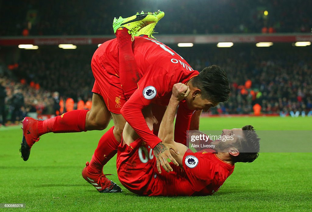 Roberto Firmino of Liverpool (L) celebrates with Adam Lallana as he scores their second goal during the Premier League match between Liverpool and Stoke City at Anfield on December 27, 2016 in Liverpool, England.