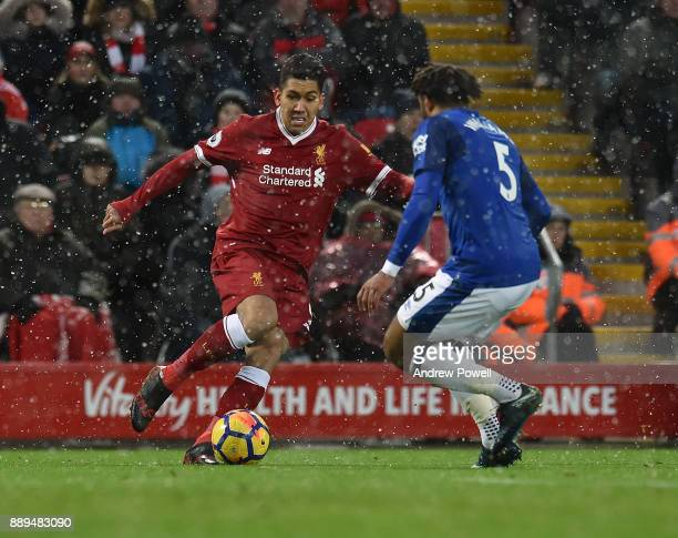 Roberto Firmino of Liverpool competes with Ashley Williams of Everton during the Premier League match between Liverpool and Everton at Anfield on...
