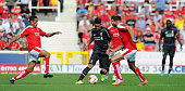Roberto Firmino of Liverpool competes with James Dayton of Swindon Town during a preseason friendly at County Ground on August 2 2015 in Swindon...