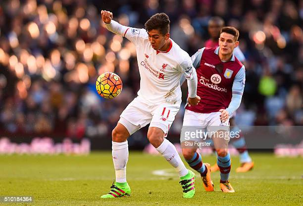 Roberto Firmino of Liverpool controls the ball under pressure from Ashley Westwood of Aston Villa during the Barclays Premier League match between...