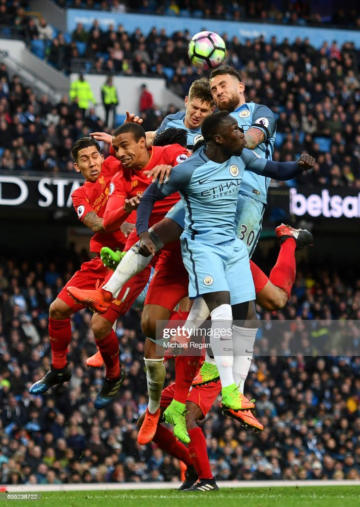 Roberto Firmino of Liverpool (L), Georginio Wijnaldum of Liverpool, John Stones of Manchester City, Nicolas Otamendi of Manchester City and Bacary Sagna of Manchester City all battle to win a header during the Premier League match between Manchester City and Liverpool at Etihad Stadium on March 19, 2017 in Manchester, England.