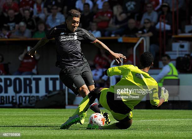 Roberto Firmino of Liverpool goes in on Lawrence Vigouroux of Swindon Town during a preseason friendly at County Ground on August 2 2015 in Swindon...