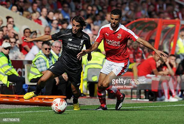 Roberto Firmino of Liverpool in action with Kevin Stewart of Swindon Town during a preseason friendly at County Ground on August 2 2015 in Swindon...