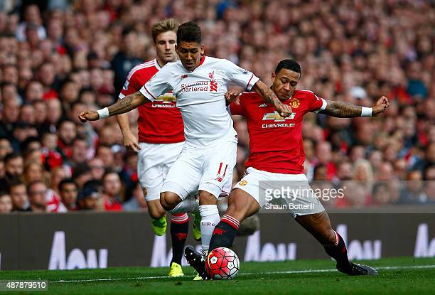 Roberto Firmino of Liverpool is challenged by Memphis Depay of Manchester United during the Barclays Premier League match between Manchester United...