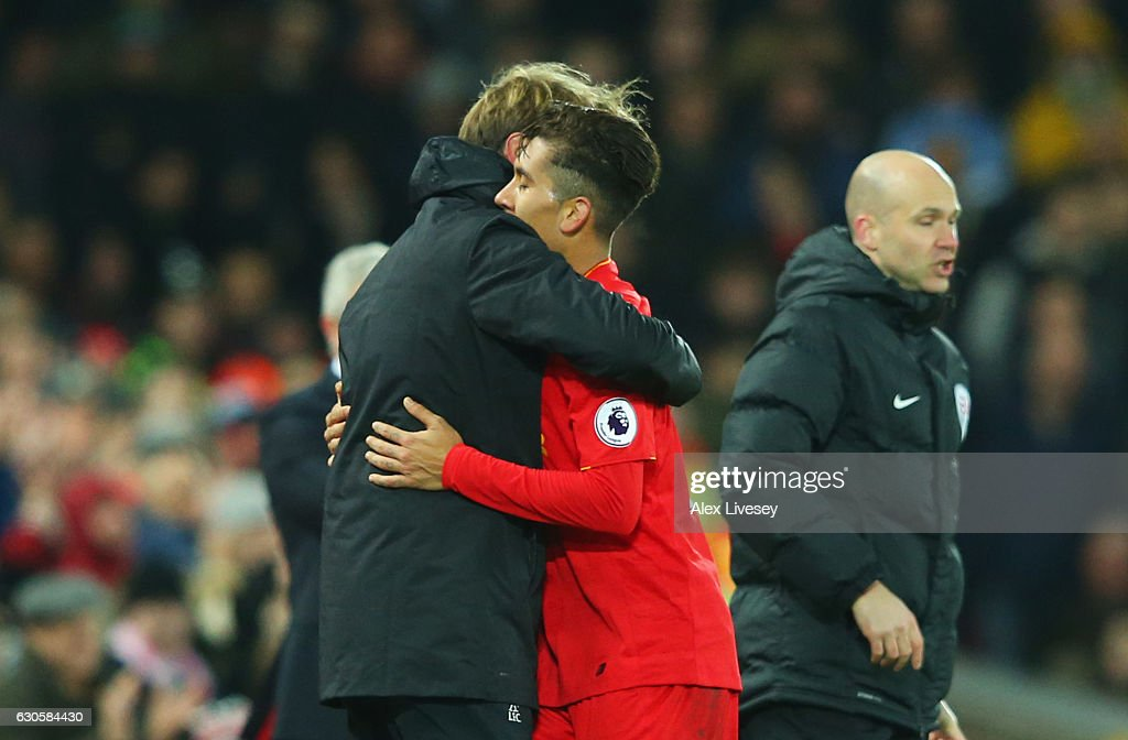 Roberto Firmino of Liverpool is embraced by Jurgen Klopp manager of Liverpool as he is substituted during the Premier League match between Liverpool and Stoke City at Anfield on December 27, 2016 in Liverpool, England.