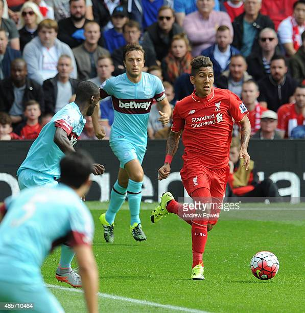 Roberto Firmino of Liverpool runs past Mark Noble of West Ham United during the Barclays Premier League match between Liverpool and West Ham United...