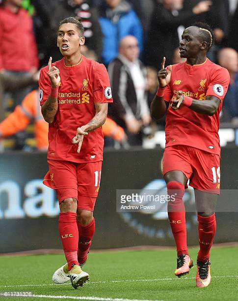 Roberto Firmino of Liverpool Scores and celebrates with his teamates after putting liverpool level at 11 during the Premier League match between...