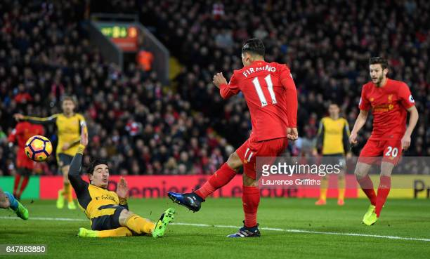 Roberto Firmino of Liverpool scores his sides first goal as Hector Bellerin of Arsenal attempts to block during the Premier League match between...