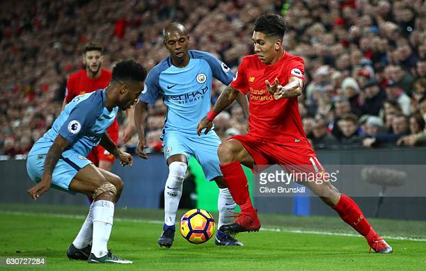 Roberto Firmino of Liverpool takes on Raheem Sterling of Manchester City during the Premier League match between Liverpool and Manchester City at...