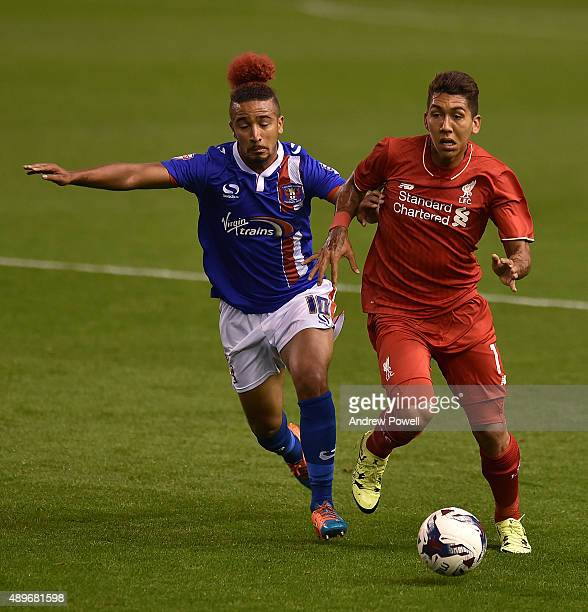Roberto Firmino of Liverpool tussles with Bastien Hery of Carlisle United during the Capital One Cup third round match between Liverpool and Carlisle...
