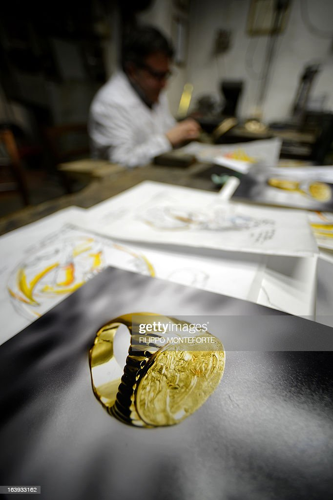 Roberto Franchi, goldsmiths who was commissioned along his brother Claudio to make the gold 'Fisherman's Ring' worn by Pope Benedict XVI when he was elected in 2005, works in his workshop on March 18, 2013. Benedict was the first pope since the 19th century to commission a 'Fisherman's Ring' -- his predecessor John Paul II wore a simple gold ring with a cross -- and he has worn the chunky gold ring at all his major public appearances. The ring is so called because it depicts Saint Peter, who was a fisherman by trade, pulling up his net from a boat. AFP PHOTO/ Filippo MONTEFORTE
