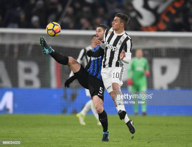 Roberto Gagliardini of FC Internazionale and Paulo Dybala of Juventus FC compete for the ball during the Serie A match between Juventus and FC...