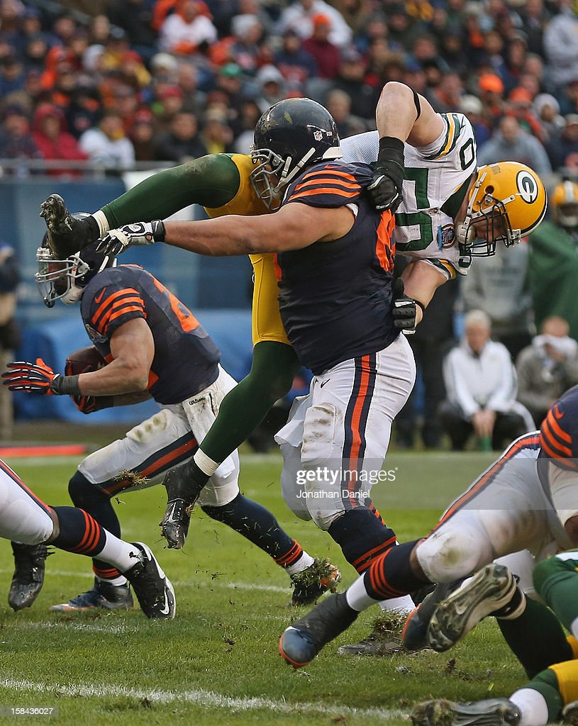 Roberto Garza #63 of the Chicago Bears flips A.J. Hawk #50 of the Green Bay Packers at Soldier Field on December 16, 2012 in Chicago, Illinois. The Packers defeated the Bears 21-13.