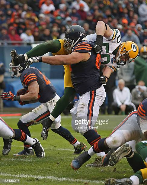 Roberto Garza of the Chicago Bears flips AJ Hawk of the Green Bay Packers at Soldier Field on December 16 2012 in Chicago Illinois The Packers...
