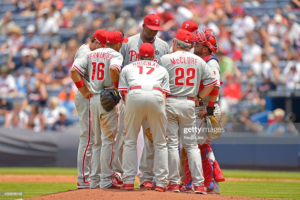 Roberto Hernandez #27 of the Philadelphia Phillies (center, back) talks with teammates and pitching coach Pete Mackanin #45 during the sixth inning against the Atlanta Braves at Turner Field on June 18, 2014 in Atlanta, Georgia. The Braves won 10-5.