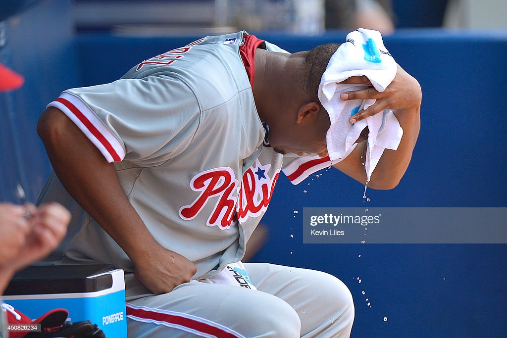 Roberto Hernandez #27 of the Philadelphia Phillies tries to stay cool by wiping his head with a wet towel on the bench during the fifth inning against the Atlanta Braves at Turner Field on June 18, 2014 in Atlanta, Georgia. The Braves won 10-5.