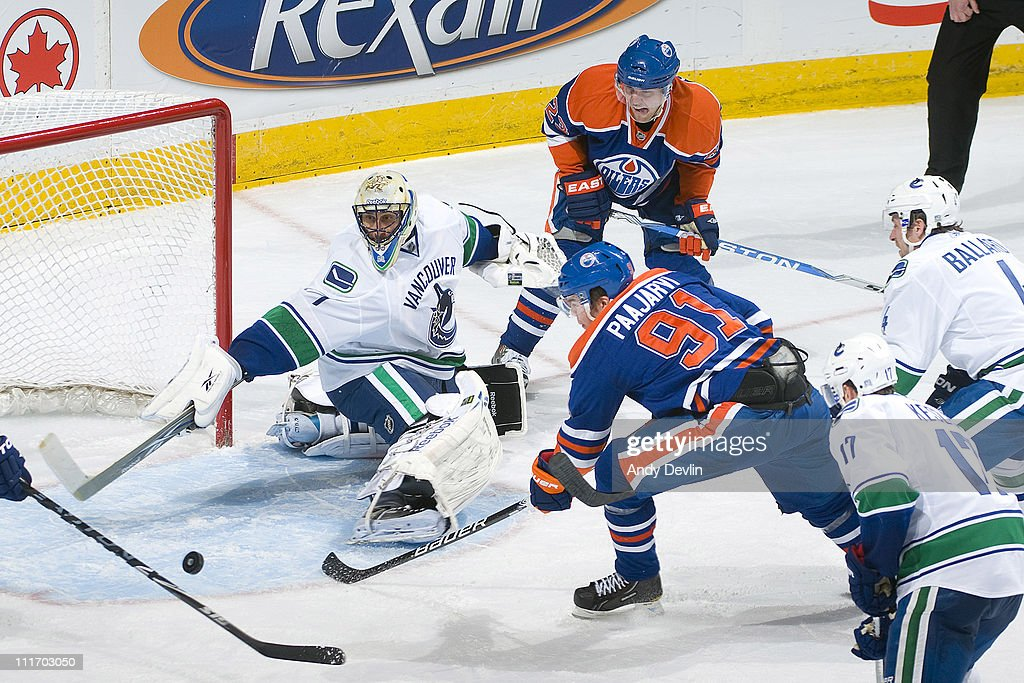 Roberto Luongo #1 of the Vancouver Canucks and Magnus Paajarvi #91 of the Edmonton Oilers reach for the puck at Rexall Place on April 5, 2011 in Edmonton, Alberta, Canada.
