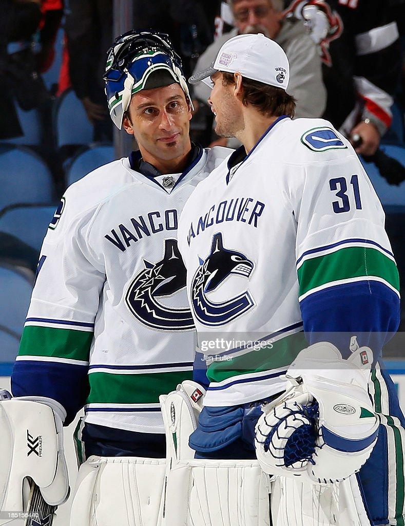 Roberto Luongo #1 of the Vancouver Canucks celebrates a shutout victory over the Buffalo Sabres with teammate Eddie Lack #31 at First Niagara Center on October 17, 2013 in Buffalo, New York. Vancouver defeated Buffalo 3-0.