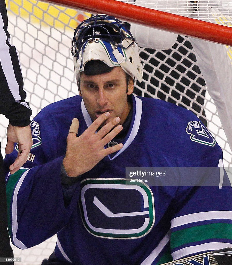<a gi-track='captionPersonalityLinkClicked' href=/galleries/search?phrase=Roberto+Luongo&family=editorial&specificpeople=202638 ng-click='$event.stopPropagation()'>Roberto Luongo</a> #1 of the Vancouver Canucks checks his lip after players crashed the net while playing the New Jersey Devils during the third period of their NHL game at Rogers Arena on October 8, 2013 in Vancouver, British Columbia, Canada.