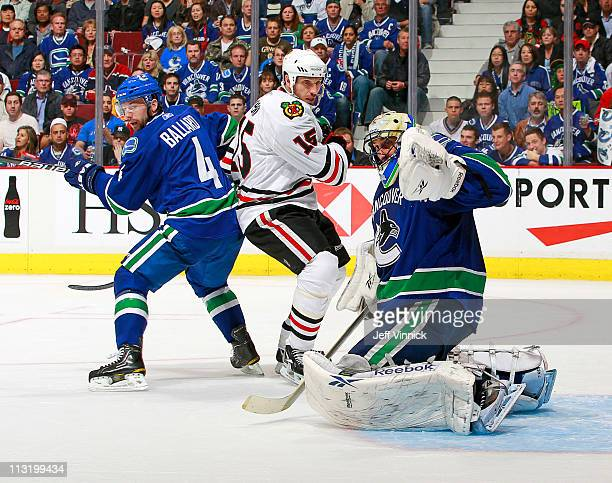 Roberto Luongo of the Vancouver Canucks follows the puck while Keith Ballard of the Vancouver Canucks and Fernando Pisani of the Chicago Blackhawks...