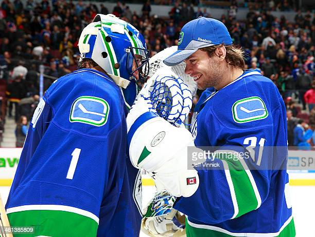 Roberto Luongo of the Vancouver Canucks is congratulated by teammate Eddie Lack during their NHL game against the Edmonton Oilers at Rogers Arena...