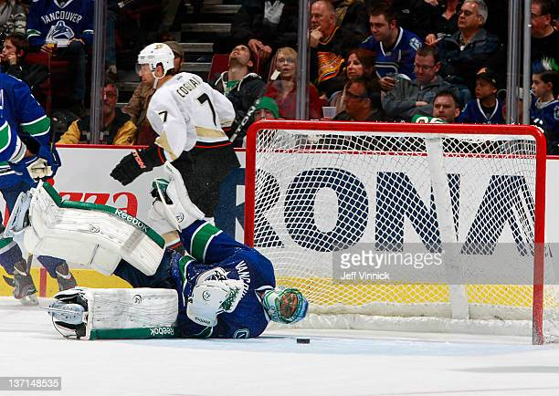 Roberto Luongo of the Vancouver Canucks is on his side while Andrew Cogliano of the Anaheim Ducks skates behind the net after a goal during their NHL...