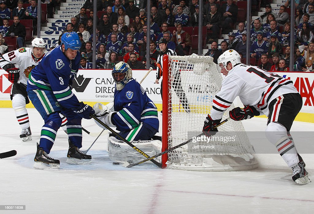 <a gi-track='captionPersonalityLinkClicked' href=/galleries/search?phrase=Roberto+Luongo&family=editorial&specificpeople=202638 ng-click='$event.stopPropagation()'>Roberto Luongo</a> #1 of the Vancouver Canucks makes a pad save on <a gi-track='captionPersonalityLinkClicked' href=/galleries/search?phrase=Jonathan+Toews&family=editorial&specificpeople=537799 ng-click='$event.stopPropagation()'>Jonathan Toews</a> #19 of the Chicago Blackhawks as <a gi-track='captionPersonalityLinkClicked' href=/galleries/search?phrase=Kevin+Bieksa&family=editorial&specificpeople=688792 ng-click='$event.stopPropagation()'>Kevin Bieksa</a> #3 of the Vancouver Canucks looks on during their NHL game at Rogers Arena February 1, 2013 in Vancouver, British Columbia, Canada. Vancouver won 2-1 in a shootout.
