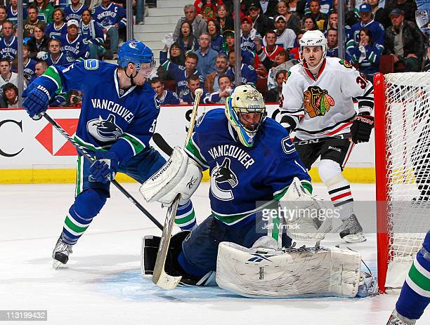 Roberto Luongo of the Vancouver Canucks makes a save while Christian Ehrhoff of the Vancouver Canucks contains Dave Bolland of the Chicago Blackhawks...