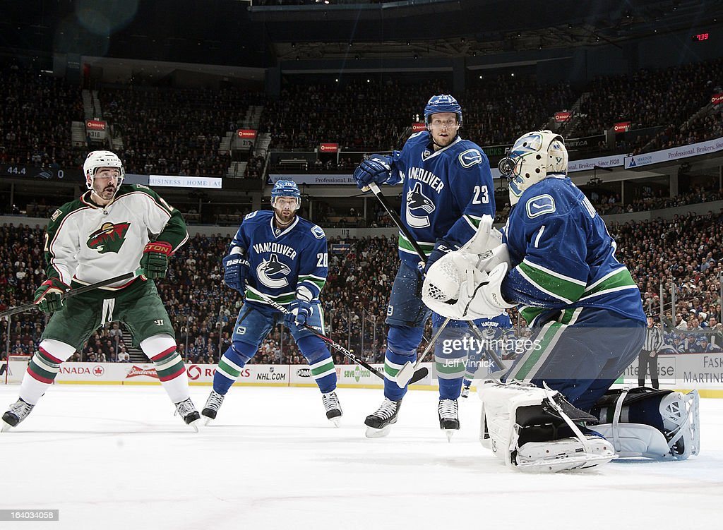 Roberto Luongo #1 of the Vancouver Canucks takes a shot off the mask from Cal Clutterbuck #22 of the Minnesota Wild while Chris Higgins #20 and Alexander Edler #23 of the Canucks watch during their NHL game at Rogers Arena March 18, 2013 in Vancouver, British Columbia, Canada.