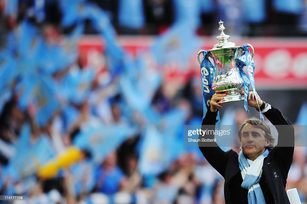 Roberto Mancini lifts the trophy after his Manchester City team wins the FA Cup sponsored by E.ON Final match between Manchester City and Stoke City at Wembley Stadium on May 14, 2011 in London, England.