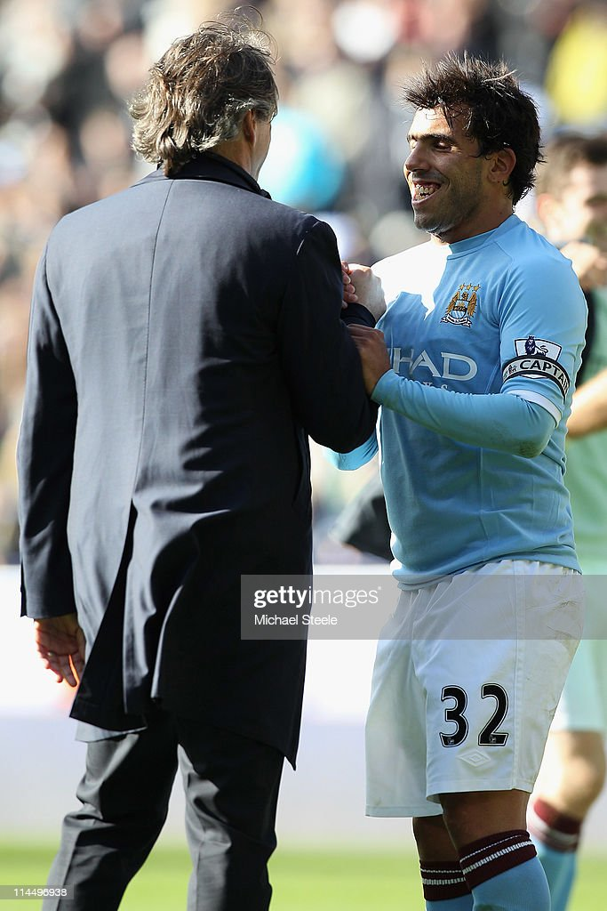 Roberto Mancini (L) manager of Manchester City shakes hands with Carlos Tevez (R) after his sides 2-0 victory during the Barclays Premier League match between Bolton Wanderers and Manchester City at the Reebok Stadium on May 22, 2011 in Bolton, England.