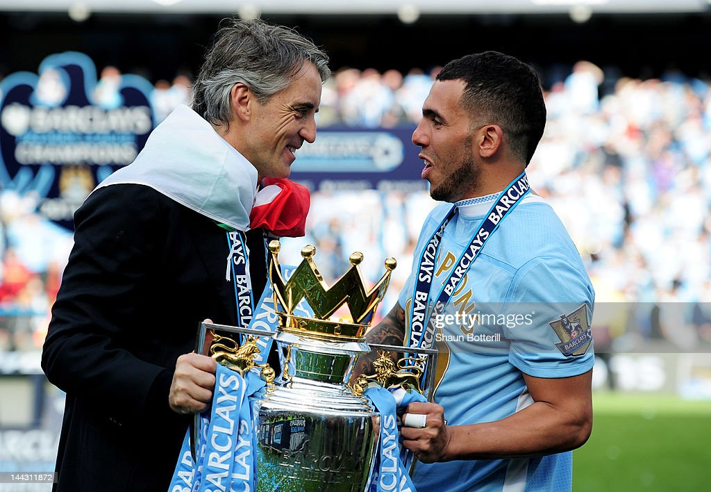 <a gi-track='captionPersonalityLinkClicked' href=/galleries/search?phrase=Roberto+Mancini&family=editorial&specificpeople=234429 ng-click='$event.stopPropagation()'>Roberto Mancini</a> the manager of Manchester City and Carlos Tevez of Manchester City celebrate with the trophy following the Barclays Premier League match between Manchester City and Queens Park Rangers at the Etihad Stadium on May 13, 2012 in Manchester, England.
