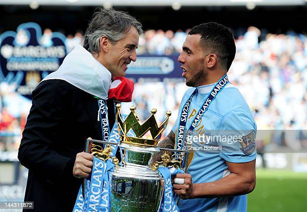 Roberto Mancini the manager of Manchester City and Carlos Tevez of Manchester City celebrate with the trophy following the Barclays Premier League...