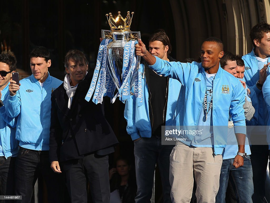 <a gi-track='captionPersonalityLinkClicked' href=/galleries/search?phrase=Roberto+Mancini&family=editorial&specificpeople=234429 ng-click='$event.stopPropagation()'>Roberto Mancini</a> the manager of Manchester City and <a gi-track='captionPersonalityLinkClicked' href=/galleries/search?phrase=Vincent+Kompany&family=editorial&specificpeople=504694 ng-click='$event.stopPropagation()'>Vincent Kompany</a> the captain lift the Barclays Premier League trophy in front of Manchester Town Hall before the start of their victory parade around the streets of Manchester on May 14, 2012 in Manchester, England.