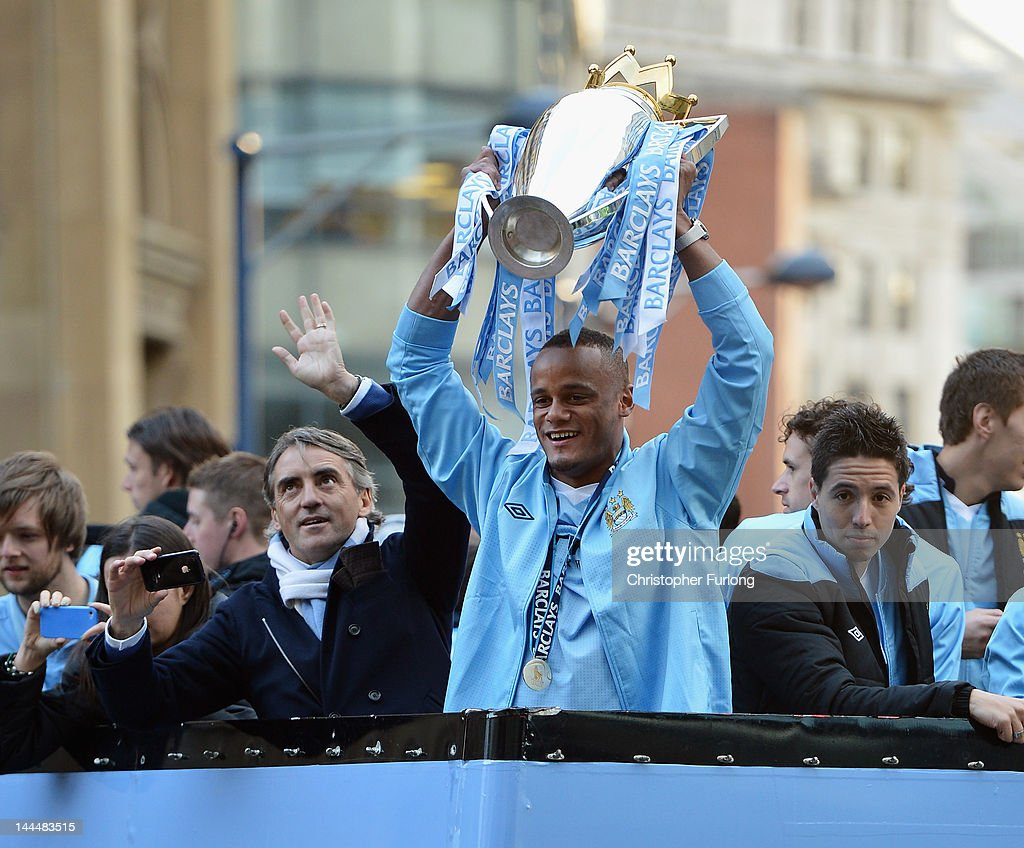 <a gi-track='captionPersonalityLinkClicked' href=/galleries/search?phrase=Roberto+Mancini&family=editorial&specificpeople=234429 ng-click='$event.stopPropagation()'>Roberto Mancini</a> the manager of Manchester City stands alongside his captain, <a gi-track='captionPersonalityLinkClicked' href=/galleries/search?phrase=Vincent+Kompany&family=editorial&specificpeople=504694 ng-click='$event.stopPropagation()'>Vincent Kompany</a> (C) and <a gi-track='captionPersonalityLinkClicked' href=/galleries/search?phrase=Samir+Nasri&family=editorial&specificpeople=648450 ng-click='$event.stopPropagation()'>Samir Nasri</a> (R) as they parade the Barclays Premier League trophy in front of thousands of fans during their victory parade around the streets of Manchester on May 14, 2012 in Manchester, England.