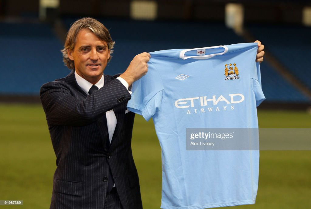 <a gi-track='captionPersonalityLinkClicked' href=/galleries/search?phrase=Roberto+Mancini&family=editorial&specificpeople=234429 ng-click='$event.stopPropagation()'>Roberto Mancini</a> the new manager of Manchester City holds up a Manchester City shirt during a photocall after a press conference held at the City of Manchester Stadium on December 21, 2009 in Manchester, England.